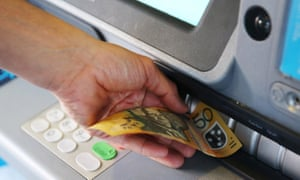 A customer withdraws a 50 Australian dollar banknote from an ATM
