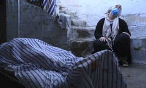 A relative cries by the body of a woman killed in shelling by the Turkish army in the town of Qamishli, Syria.