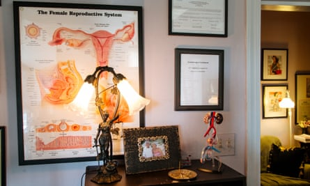 Diagrams and models of male and female reproductive systems sit next to incense and a photo of Dr Runels' parents.
