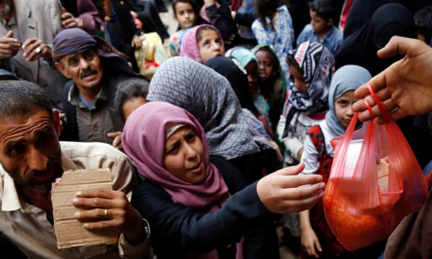 People receive food handouts in Yemen, where the UN says 83% of the population is affected by poverty
