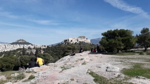 In a first, the 5th century BC Acropolis is closed. With few other places to go, Athenians take in the site on rocks beneath the ancient site.