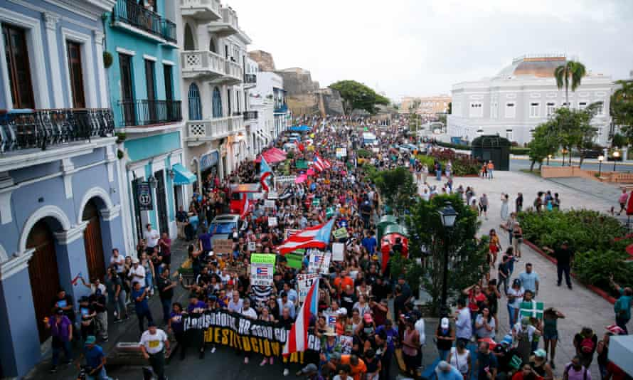 Thousands march to the Capitol building and the governor's mansion on Monday in San Juan.