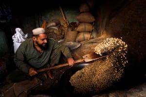 A shopkeeper tosses a pan of peanuts in Peshawar, Pakistan