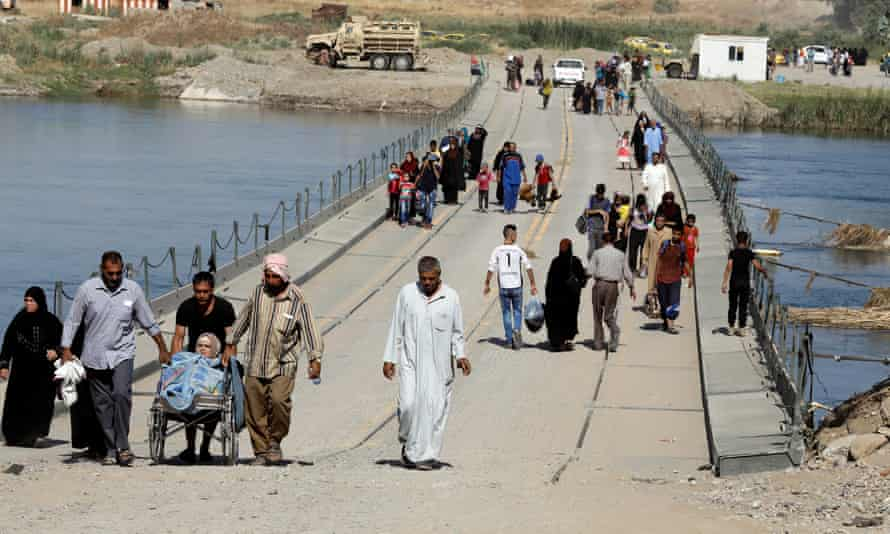 Displaced Iraqi residents cross a military pontoon bridge in western Mosul.