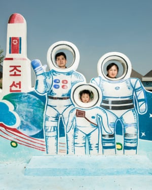 A family pose behind a tribute to the North Korean space programme at Munsu water park (October 2017)