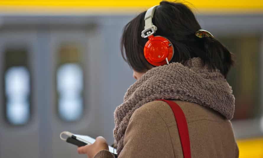 Woman listening to something on headphones and looking at smartphone.