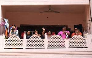Family members in self-confinement stand on a balcony in Amritsar