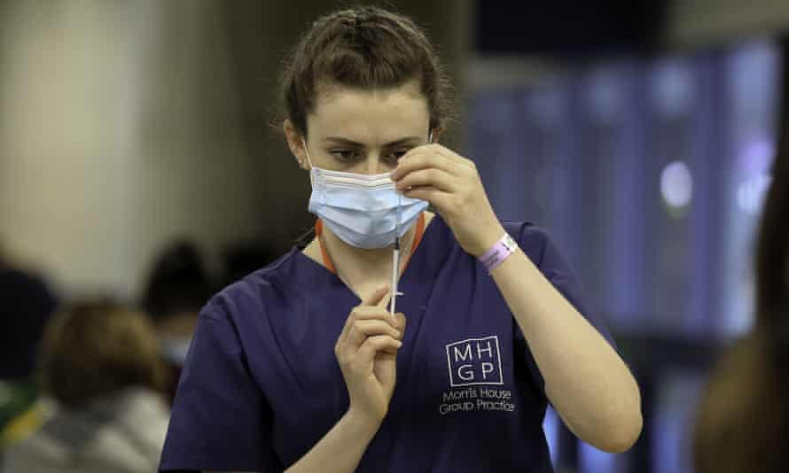 A medic prepares a Pfizer Covid-19 vaccine at the Tottenham Hotspur Stadium, London.
