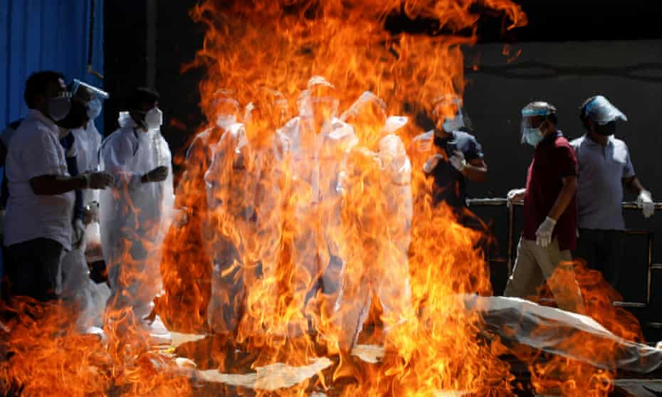Relatives wearing personal protective equipment attend the funeral of a man who died from  coronavirus, at a crematorium in New Delhi.