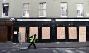 A worker walks past a boarded up pizza bar in Soho in London, 21 March 2020.
