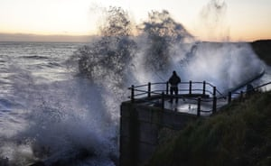 Durham, UK. A fisherman is soaked by waves as they hit the sea wall in the harbour town of Seaham