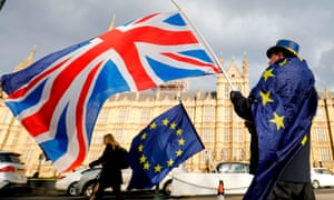 An anti-Brexit demonstrator waves a Union flag alongside a European Union flag outside the Houses of Parliament in London