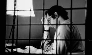 Philip Roth sitting at typewriter seen through panes of window, at Yaddo artist's retreat, 1968.
