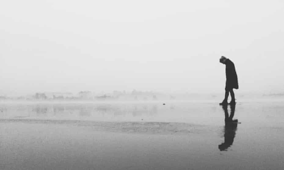 Woman walking along on beach - black and white