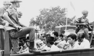 Members of the Youth Wing of the Indonesian Communist party are guarded by soldiers as they are taken by open truck to prison in Jakarta, 1965.