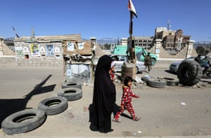 A Yemeni woman and her children pass a Houthi checkpoint amid heightened security in Sana'a, Yemen, on 27 December 2016.