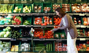 Woman shopping in a large supermarket fruit and vegetables department.