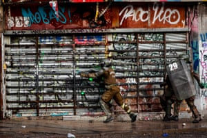 Police officers clash with protesters during another day of social mobilisation in Santiago.