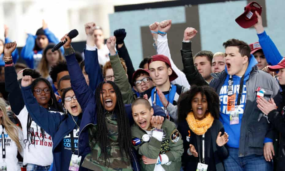 Tyra Hemans and Emma Gonzalez, from Marjory Stoneman Douglas high school in Parkland, Florida, and Naomi Wadler of Alexandria, Virginia, sing along with other students and shooting survivors at the conclusion of the March for Our Lives event in Washington DC on 24 March 2018.