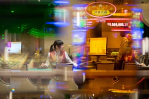 A dealer sits at a blackjack table on the gaming floor of the MGM Cotai casino and resort a few hours before opening in Macau.