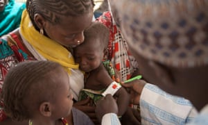 An health official measures the arm circumference of a child at a Unicef clinic near Diwka, Borno State, in February 2017.