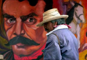 A protesting farmer stands in front of a mural with the face of Emiliano Zapata in the town square of San Salvador Atenco, Mexico.