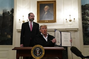 Tight-lipped George Washington and health secretary Alex Azar in the White House watch over the president holding up the $8.3 billion bill he just signed to fund US efforts o fight the coronavirus outbreak.