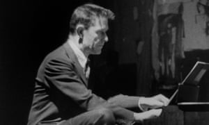 John Cage playing a children's size piano in 1960.