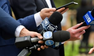 Reporters' hands holding microphones at a press conference