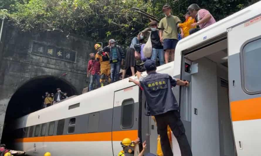 Rescue teams help passengers to get off the roof of the train.