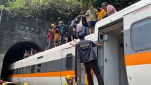 Rescuers help passengers down from the roof of a derailed train in Hualien, Taiwan