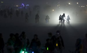 Participants ride bikes across the Playa to the burning of the Temple of Promise