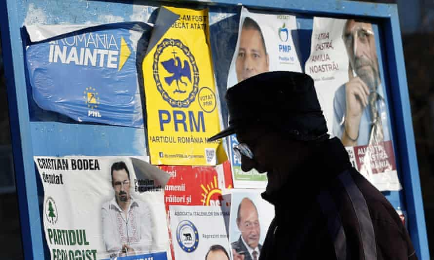 A Romanian man walks by a display board full of election posters depicting various party candidates before Sunday's elections