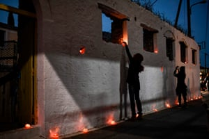 People decorate a street with candles inside oranges at an Eastern Orthodox Easter ceremony