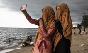 Veiled Thai women take a selfie on Talo Kapo beach in the south of the country while enjoying Eid al-Fitr, which marks the end of Ramadan.