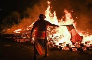A man burns an Irish flag in the Sandy Row area