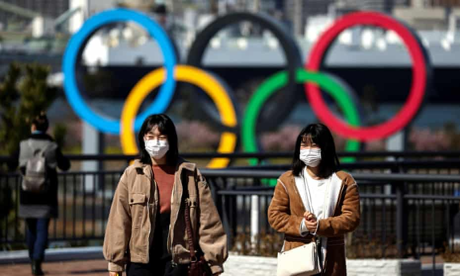 People wear face masks in Tokyo as a Japanese woman was diagnosed with Covid-19 for the second time.