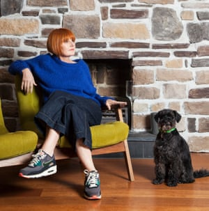 Mary Portas in an electric blue jumper, cropped wide-bottom jeans and trainers sitting cross-legged on her sofa at her home, a bare brick wall behind her and her black dog next to the sofa