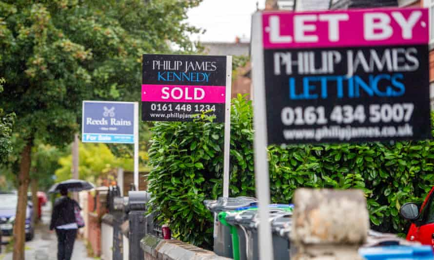 A picture of estate boards outside homes in Manchester.