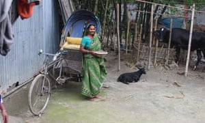 Tulsi stands in the courtyard of her hut in the village of Outpara in Bangladesh