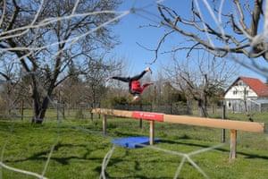 Gymnast Clara Neumann trains on the balance beam in her parent's garden in Dresden, Germany.