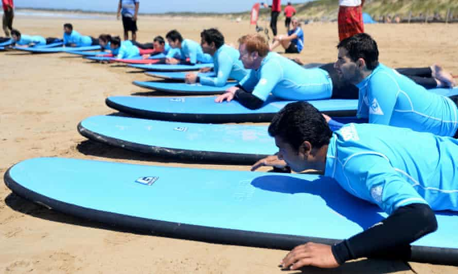 International students from Deakin University learning to surf. Universities must focus on improving student experience if foreign student numbers are to be maintained according to a new report.