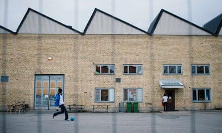 Refugees play football outside their shelter in Sundbyberg, Sweden