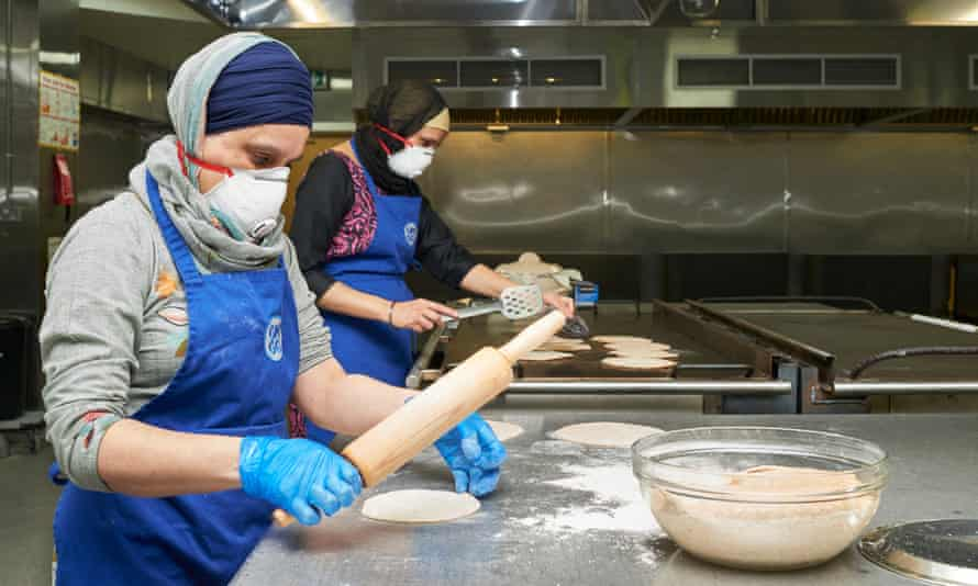 Two people in masks making chapatis in a kitchen.