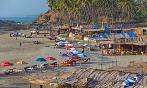 Daylight, and tourists enjoy relaxing on the sand at Vagator Beach, Goa.