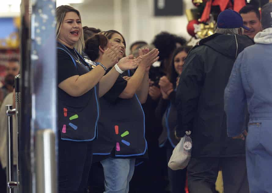 Walmart employees cheer to welcome customers during the store's opening.