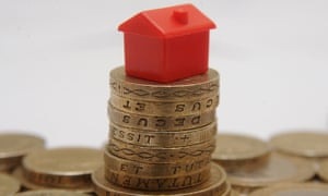 a plastic model of a house sitting on a pile of one pound coins,