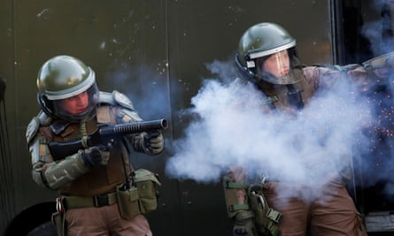 Security forces aim their weapons during a protest in Santiago.