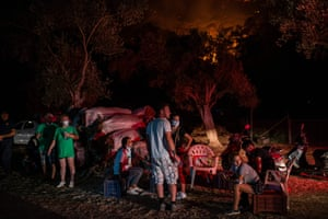 People wait near wildfires in a rural area of Marmaris district, Turkey