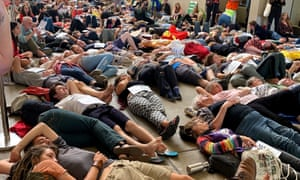 Extinction Rebellion protesters lie down during a staged 'die-in' at the Queensland Museum in Brisbane